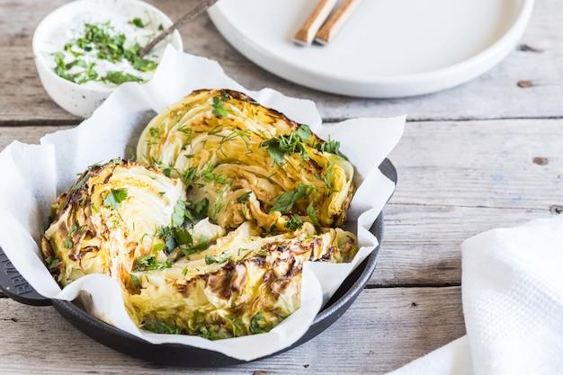 Pieczone plastry kapusty. dieta wegańska. zdrowe steki z grillowanej kapusty z sosem, przyprawami i ziołami.