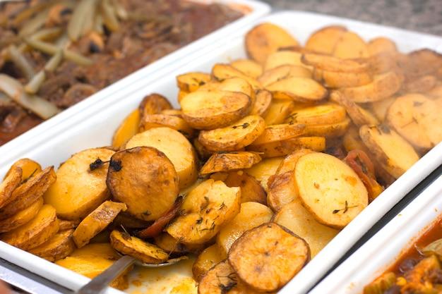 Pieczone plastry ziemniaków na białej tacy z łyżką