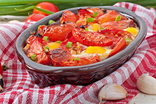 Pieczone pomidory z czosnkiem i jajkami ozdobione zieloną cebulą