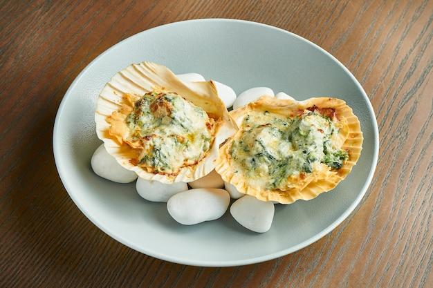 Pieczone przegrzebki z serem na morzu, gorące kamienie na drewnianej powierzchni. zdrowe owoce morza. efekt filmowy podczas postu. nieostrość