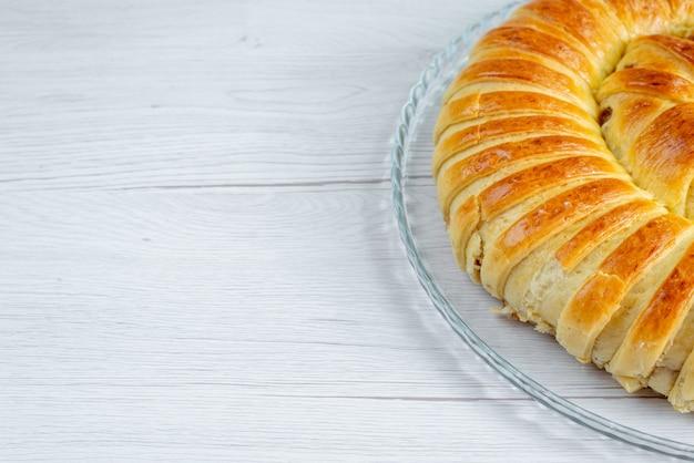 Pieczone pyszne ciasto bransoletka uformowana w szklanym talerzu na lekkim biurku, ciasto biszkoptowe słodki cukier do pieczenia