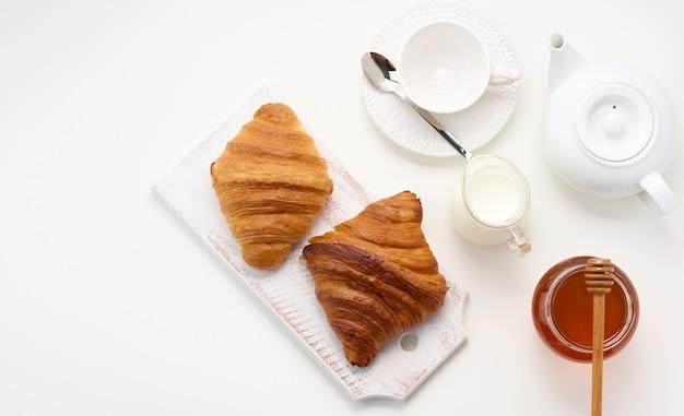 Pieczone rogaliki, biały ceramiczny czajniczek i pusty kubek i spodek, słoik miodu na białym stole, widok z góry. śniadanie