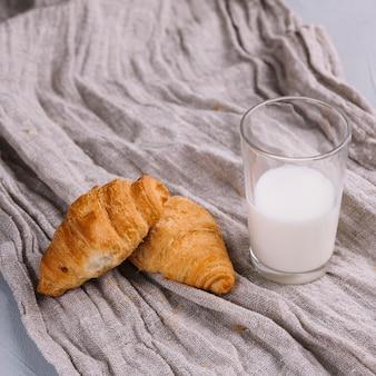 Pieczone rogaliki i szklanka mleka na zmiętej tkaninie worek