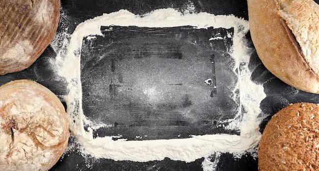 Pieczone różne bochenki chleba na czarnym tle