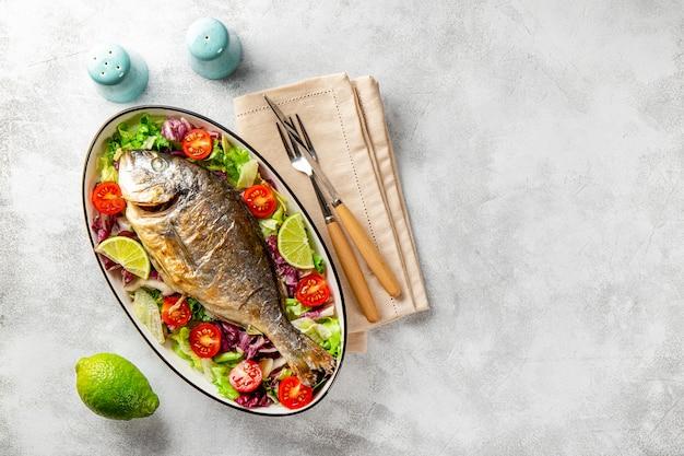 Pieczone ryby dorado całe na talerzu ze świeżymi warzywami na jasnoszarym tle widok z góry miejsca kopiowania tekstu. zdjęcie wysokiej jakości