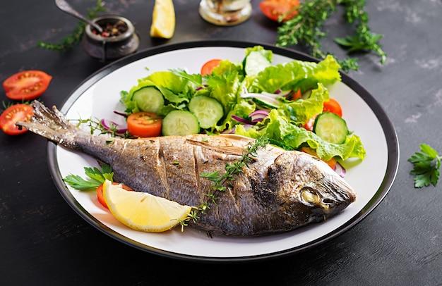 Pieczone ryby dorado z cytryną i świeżą sałatką w białym talerzu na ciemnym tle rustykalnym. zdrowy obiad z koncepcją ryb. diety i czyste jedzenie