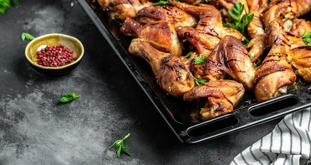 Pieczone skrzydełka i udka z kurczaka na blasze do pieczenia