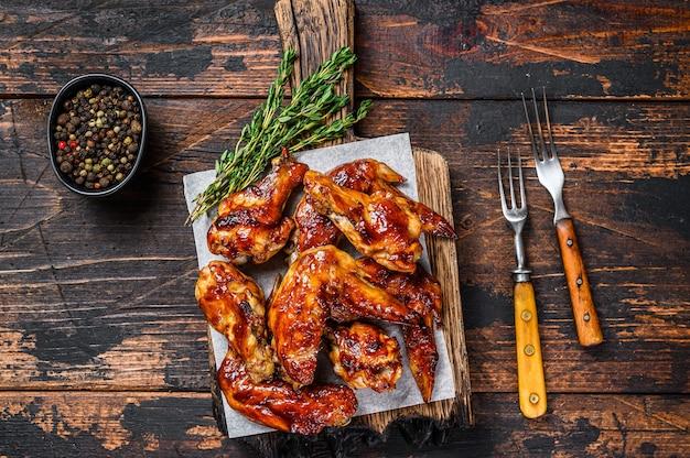 Pieczone skrzydełka kurczaka bbq z sosem dipowym. ciemne drewniane tło. widok z góry.