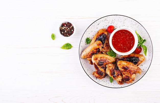 Pieczone skrzydełka z kurczaka w stylu azjatyckim i sosem pomidorowym na talerzu