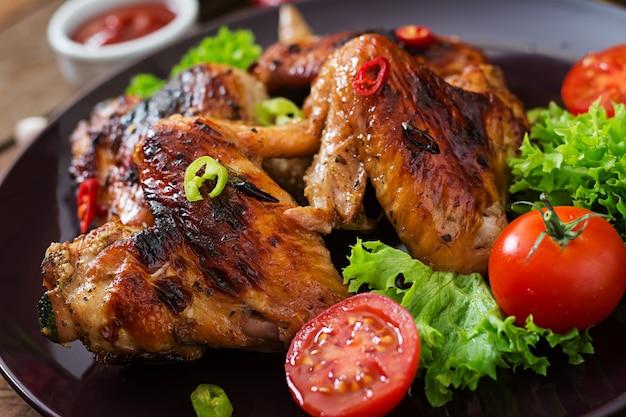 Pieczone skrzydełka z kurczaka w stylu azjatyckim na talerzu.