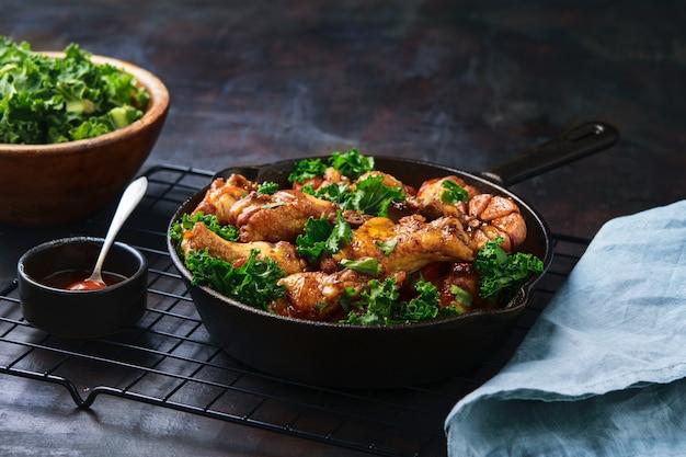 Pieczone skrzydełka z kurczaka z marchewką, jarmużem, czosnkiem i sosem zanurzeniowym w żelaznej patelni.