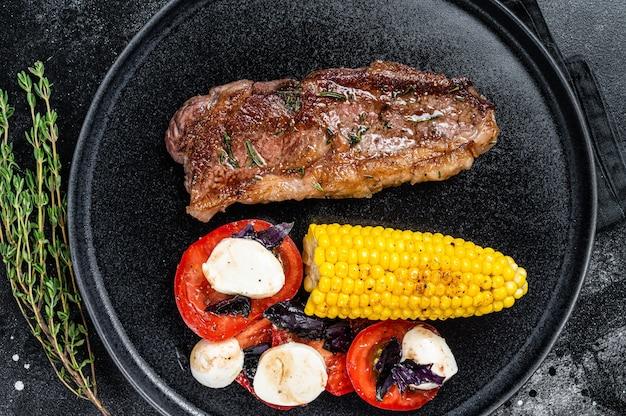 Pieczone steki z wołowiny p rostbef lub new york na talerzu z dodatkami. czarne tło. widok z góry.