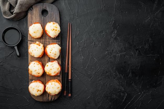 Pieczone sushi maki roladki z łososiem, krabem, ogórkiem, awokado, ikrą latającej ryby i ostrym sosem zestaw na czarnym kamieniu