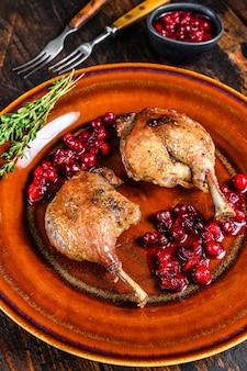 Pieczone świąteczne udka z kaczki z sosem żurawinowym.