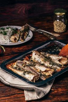 Pieczone tuszki rybne na blasze do pieczenia na powierzchni drewnianej