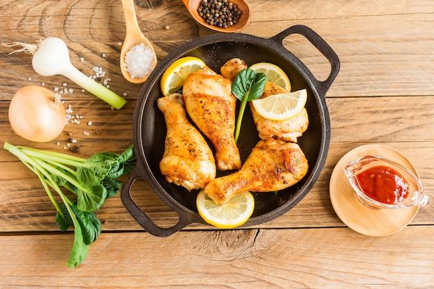 Pieczone udka z kurczaka i rozmaryn na czarnej patelni. gotowane z sosem z pomidorów.
