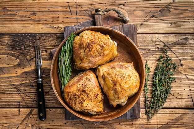 Pieczone udka z kurczaka na drewnianym talerzu z rozmarynem i ziołami. drewniany stół. widok z góry.
