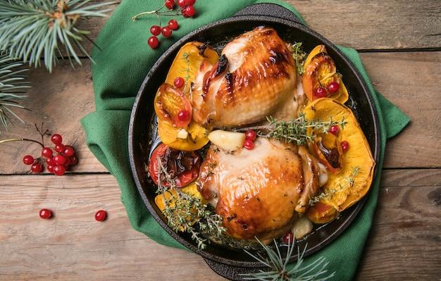 Pieczone udka z kurczaka z dynią na świąteczny obiad. świąteczny zdobiony drewniany stół