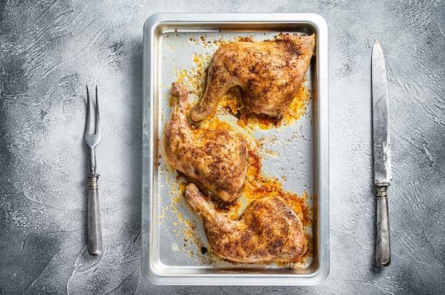 Pieczone udka z kurczaka z grilla w naczyniu do pieczenia. białe tło. widok z góry.
