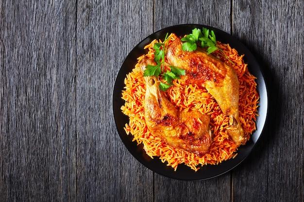 Pieczone udka z kurczaka z południowoindyjskim ryżem z pomidorami długoziarnistymi gotowanymi ze smażonymi pomidorami, cebulą, czerwonym chili w proszku, cynamonem, kurkumą na czarnym talerzu, na rustykalnym drewnianym stole, miejsce na kopię