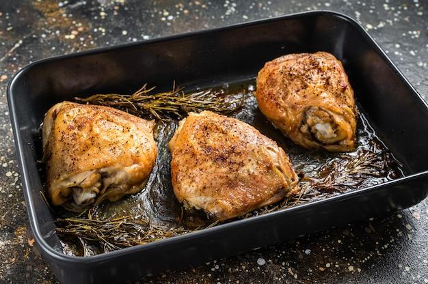 Pieczone udka z kurczaka z przyprawami w naczyniu do pieczenia. widok z góry.
