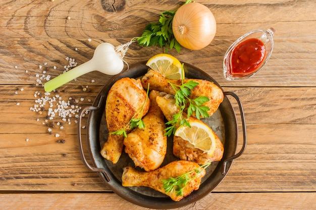 Pieczone udka z kurczaka z warzywami korzeniowymi, cytryną, czosnkiem, na patelni, na drewnianym tle