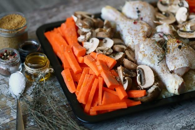 Pieczone udka z warzywami i grzybami na blasze do pieczenia.