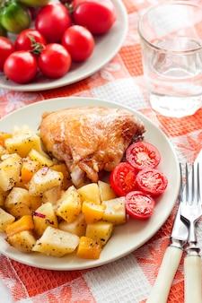 Pieczone udko z kurczaka z pieczonymi ziemniakami i ozdobą dyniową na talerzu