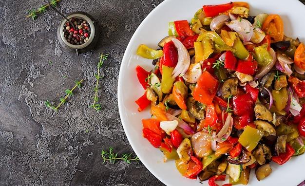 Pieczone warzywa na białym talerzu. bakłażan, cukinia, pomidory, papryka i cebula. widok z góry