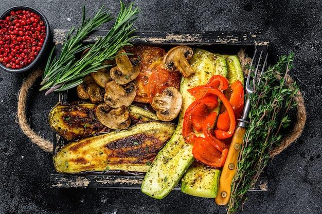 Pieczone warzywa papryka, cukinia, bakłażan i pomidor na drewnianej tacy