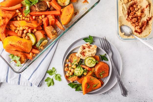 Pieczone warzywa z ciecierzycy i hummusu. płaskie świeckie wegańskie jedzenie.