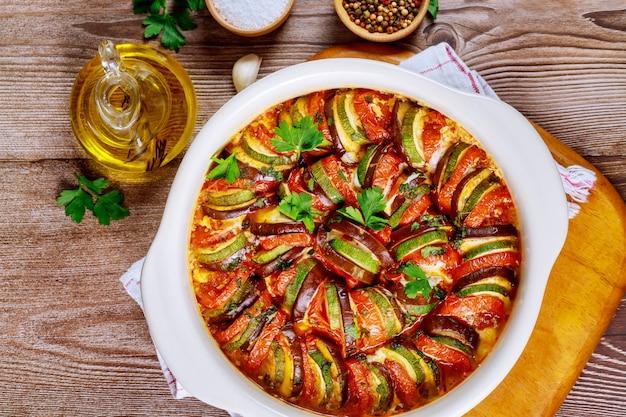 Pieczone warzywo z sosem pomidorowym w białej misce piekarnika