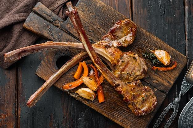 Pieczone żeberka jagnięce z czosnkiem i ziołami, na drewnianej desce do serwowania, na starym ciemnym drewnianym stole, widok z góry na płasko