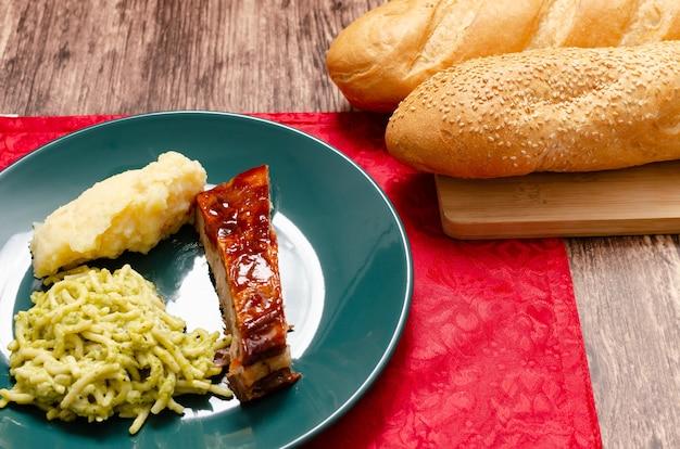 Pieczone żeberka marynowane w sosie barbecue podawane z puree ziemniaczanym spaghetti i pieczywem