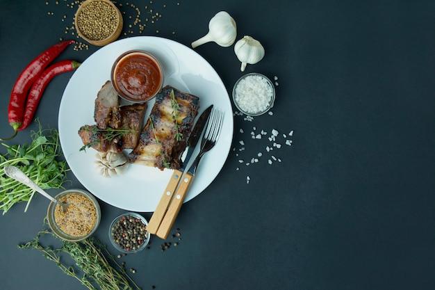 Pieczone żeberka w kolorze białym b. grillowane żeberka wieprzowe z przyprawami i świeżymi ziołami. ciemne tło miejsce na tekst. menu tła tabeli.