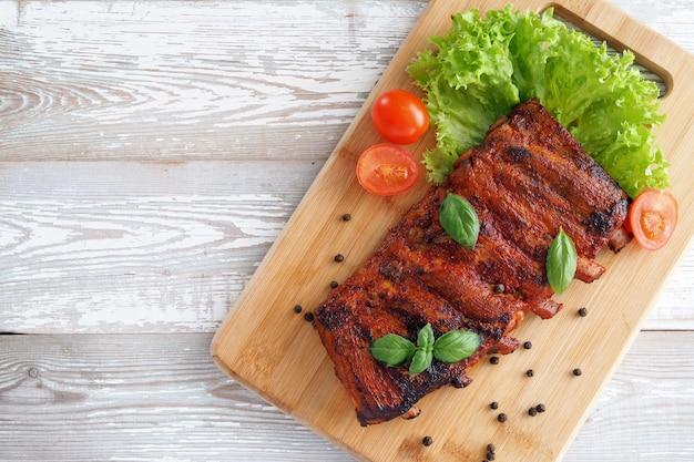 Pieczone żeberka w sosie barbecue z ziołami i pomidorami na desce. widok z góry.