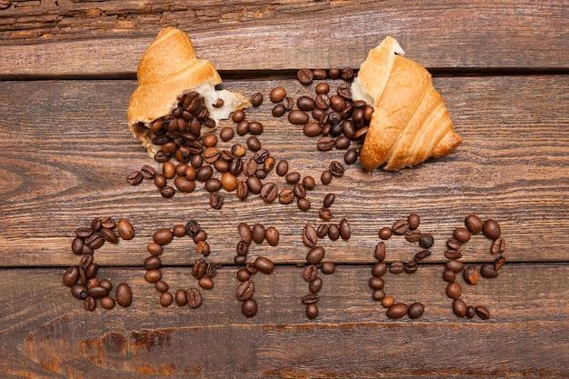 Pieczone ziarna kawy w rogaliku na drewnianym tle. zbliżenie nadzienia nasion na ciemny brąz tabeli. widok z góry. koncepcja dodatkowej energii