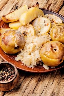 Pieczone ziemniaki, jabłka i kapusta kiszona.