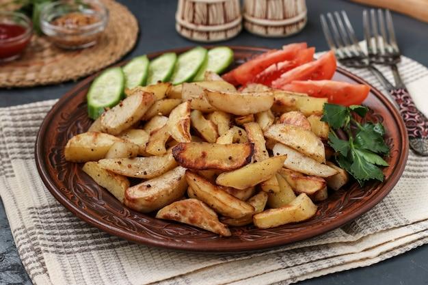 Pieczone ziemniaki podawane z pomidorami, ogórkami i natką pietruszki na talerzu na ciemnym tle, orientacja pozioma