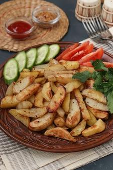 Pieczone ziemniaki podawane z pomidorami, ogórkami i natką pietruszki na talerzu na ciemnym tle