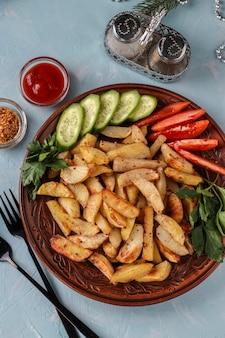 Pieczone ziemniaki podawane z pomidorami, ogórkami i natką pietruszki na talerzu, widok z góry, orientacja pionowa