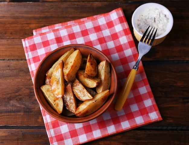 Pieczone ziemniaki w misce i sosie na stole z bliska