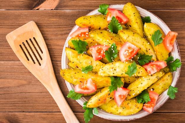 Pieczone ziemniaki w skórce z pomidorami, ziołami, przyprawami i sezamem w talerzu, widok z góry