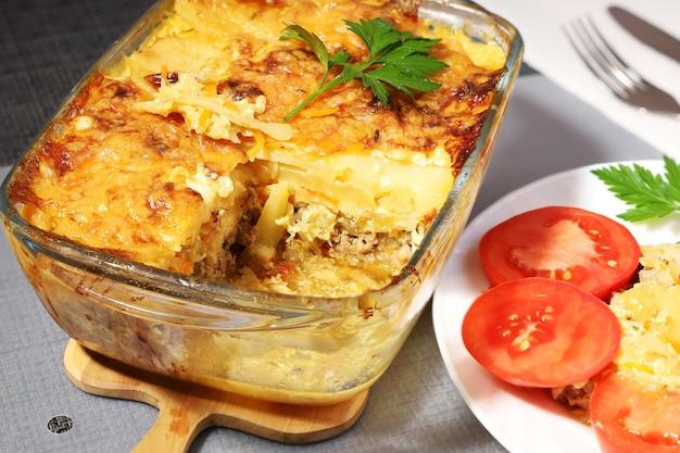 Pieczone ziemniaki z mięsem w szklanym pojemniku, podświetlona porcja przy talerzu z pomidorami