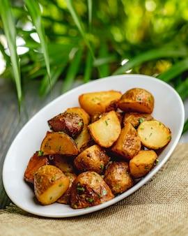 Pieczone ziemniaki z ziołami na białym talerzu