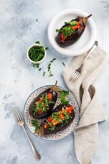 Pieczony bakłażan faszerowany z różnymi warzywami, pomidorem, papryką, cebulą i pietruszką na szarym tle kamiennego lub betonowego stołu. widok z góry