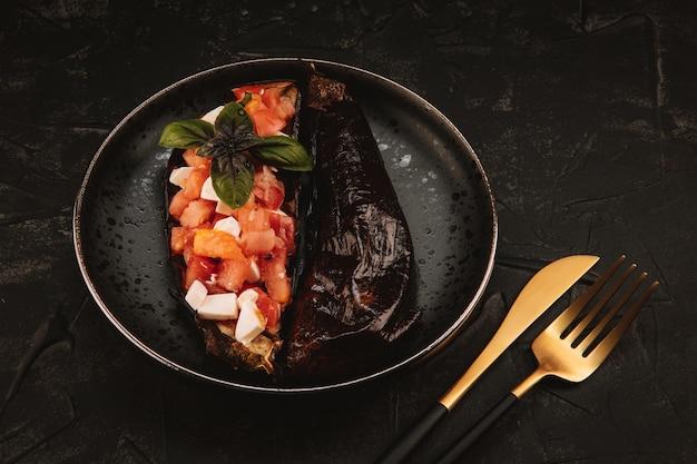 Pieczony bakłażan z sałatką pomidorową, serem feta i bazylią na czarnym talerzu
