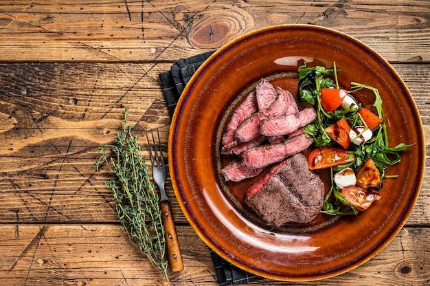 Pieczony bbq oyster top blade lub płaski stek z rostbefu na talerzu z sałatką.