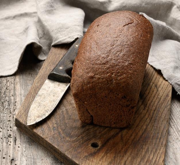 Pieczony chleb prostokątny z mąki żytniej na desce brązowej, zdrowa żywność
