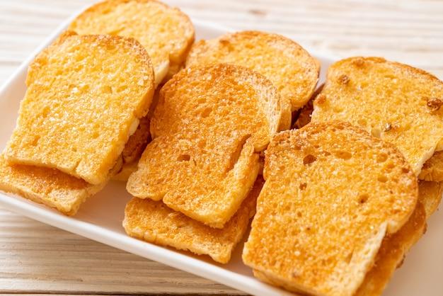 Pieczony chrupiący chleb z masłem i cukrem na talerzu